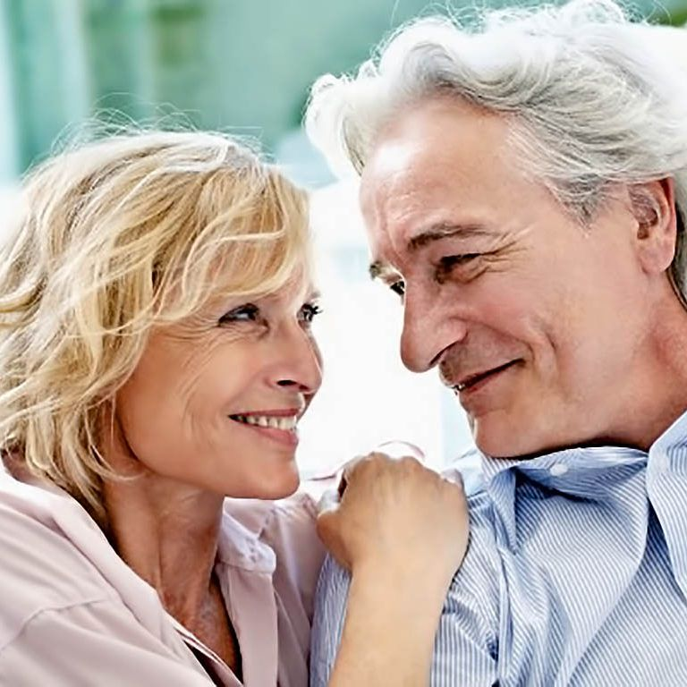 Portrait of smiling middle-aged couple looking face to face --- Image by © Oliver Rossi/Corbis